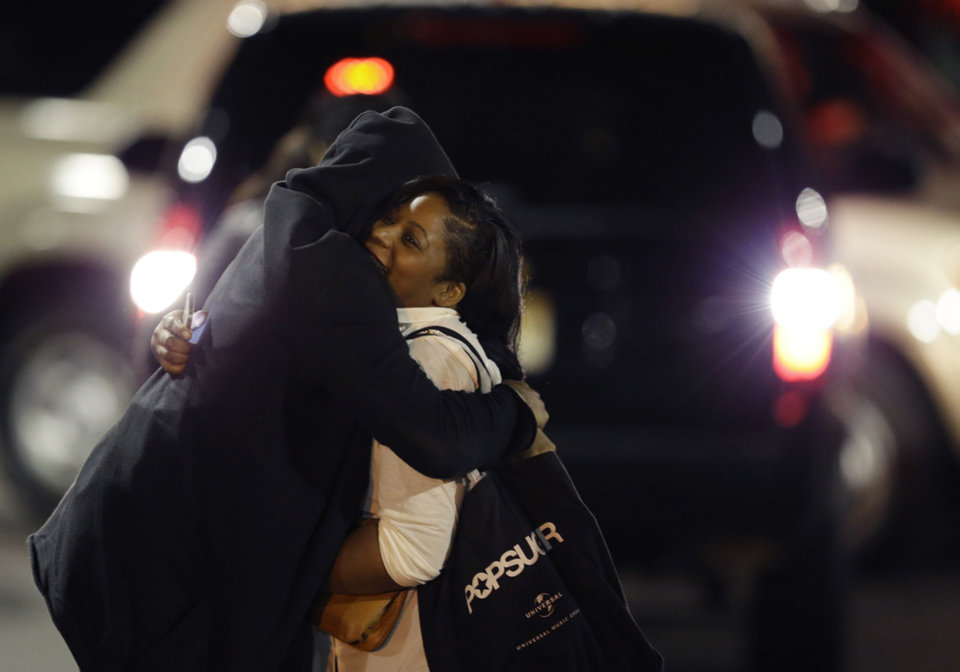 Photo - A woman, right, is reunited with a man in the parking lot of Garden State Plaza Mall following reports of a shooter, Tuesday, Nov. 5, 2013, in Paramus, N.J. Hundreds of law enforcement officers converged on the mall Monday night after witnesses said multiple shots were fired there. (AP Photo/Julio Cortez)