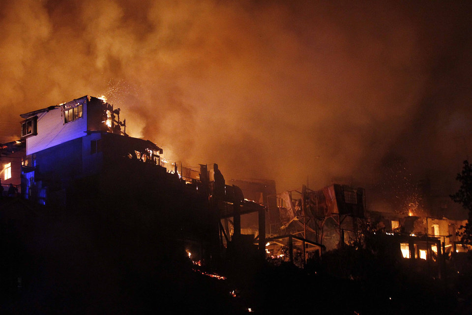 Photo - An out of control forest fire destroys homes in the city of Valparaiso, Chile, Sunday April 13, 2014. Authorities say the forest fire has destroyed at least 150 homes and is forcing evacuations. ( AP Photo/ Luis Hidalgo)