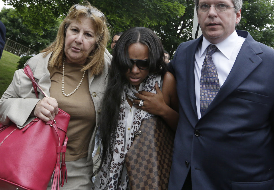 Photo - Shayanna Jenkins, middle, fiancee of former New England Patriots football player Aaron Hernandez, is escorted by attorney Janice Bassil, left, and an unidentified attorney after a bail hearing in Fall River Superior Court Thursday, June 27, 2013 in Fall River, Mass. Hernandez, charged with murdering Odin Lloyd, a 27-year-old semi-pro football player, was denied bail. (AP Photo/Elise Amendola)