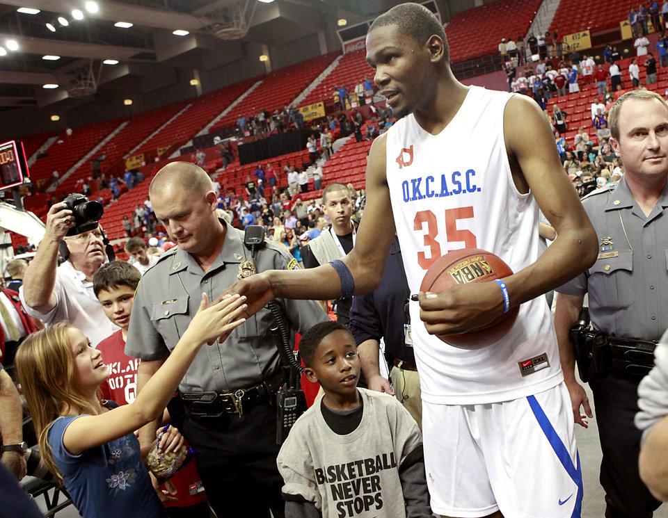 Photo - Kevin Durant high fives Hannah Segell, age 11, of Oklahoma City, as he leaves the court following the US Fleet Tracking Basketball Invitational at the Cox Convention Center in Oklahoma City Sunday, Oct. 23, 2011. The White Team defeated the Blue Team 176-171. Photo by John Clanton, The Oklahoman