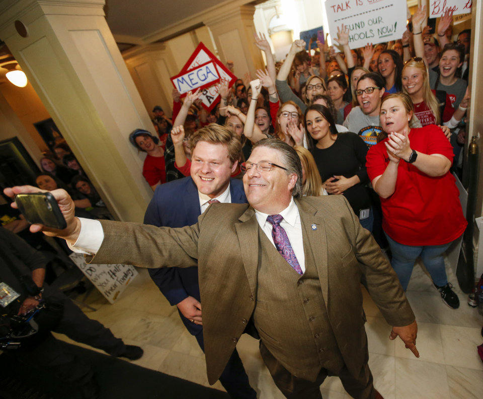 Photo - Rep. Forrest Bennett, D-Oklahoma City, left, and Rep. Scott Fetgatter, R-Okmulgee, take a selfie in front of teachers, students and supporters of increased education funding who were rallying in front of the entrance to the House chamber of the fourth floor during the third day of a walkout by Oklahoma teachers at the state Capitol in Oklahoma City, Wednesday, April 4, 2018. Photo by Nate Billings, The Oklahoman