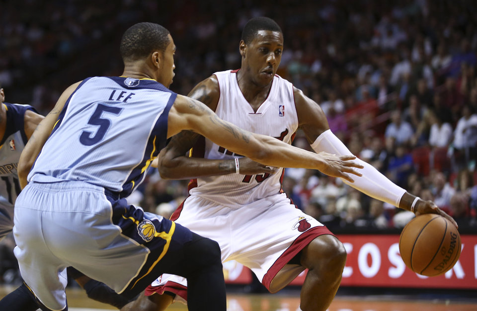 Photo - Memphis Grizzleies' Courtney Lee (5) tries to steal the ball from Miami Heat's Mario Chalmers (15) during the first half of an NBA basketball game in Miami, Friday, March 21, 2014. (AP Photo/J Pat Carter)