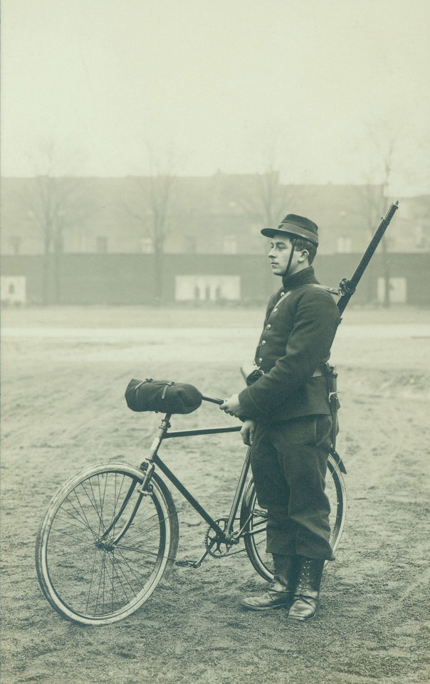 Photo - In this undated photo provided by the WielerMuseum Roeselare, a Belgian World War I soldier with his bicycle in Belgium during wartime. Late in the 19th century the Belgian Army took an interest in the newly emerging sport of cycling. A separate unit was created and came to be known as the Cyclist Riflemen. During World War I they played a key role in the Battle of Haelen in Belgium. The German Army nicknamed them the Black Devils, owing to their black outfits and hats, as well as their fast silent movements. (AP Photo/WielerMuseum)