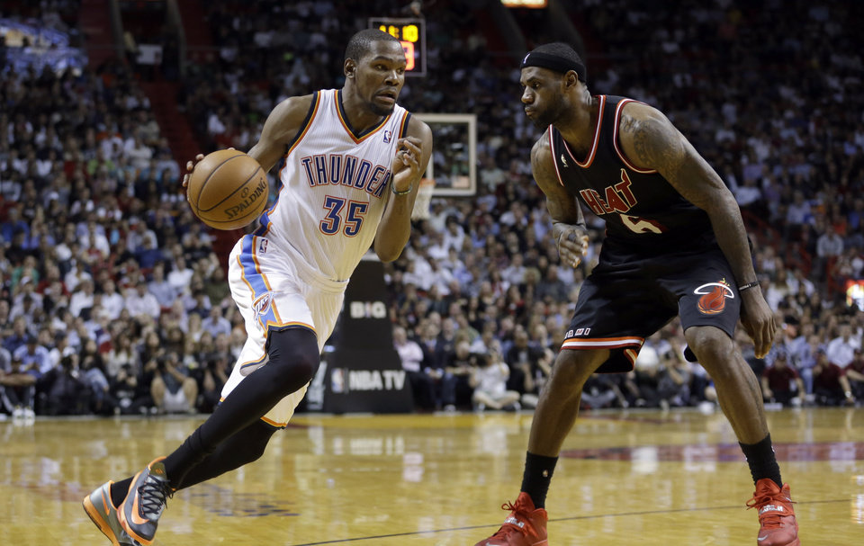 Photo - Oklahoma City Thunder small forward Kevin Durant (35) drives against Miami Heat small forward LeBron James (6) during the fourth quarter of an NBA basketball game in Miami, Wednesday, Jan. 29, 2014. The Thunder won 112-95. (AP PhotoAlan Diaz)