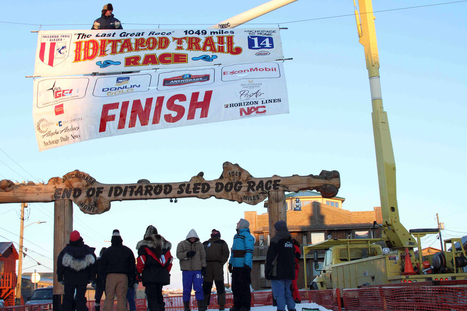 Photo - The Iditarod Trial Sled Dog Race finish banner is raised above the burled arch finish line in Nome, Alaska, on Monday, March 10, 2014. The race winner is expected some time early Tuesday, March 11, 2014. (AP Photo/Mark Thiessen)