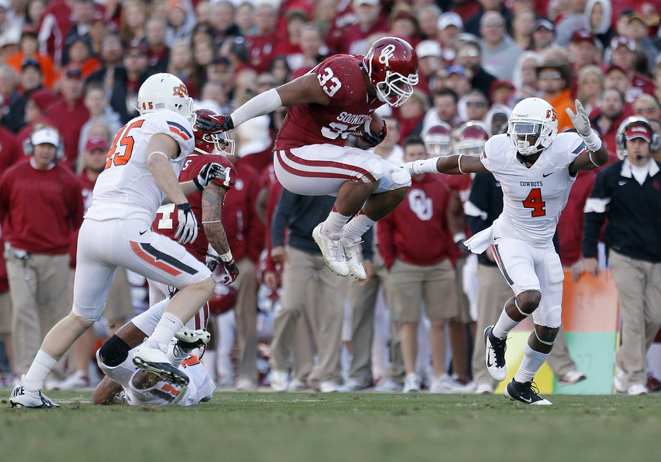 Oklahoma\'s Trey Millard (33) leaps in between Oklahoma State\'s Caleb Lavey (45) and Justin Gilbert (4) during the Bedlam college football game between the University of Oklahoma Sooners (OU) and the Oklahoma State University Cowboys (OSU) at Gaylord Family-Oklahoma Memorial Stadium in Norman, Okla., Saturday, Nov. 24, 2012. Photo by, Sarah Phipps The Oklahoman