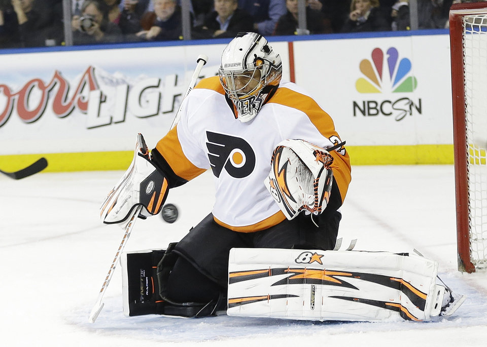 Photo - Philadelphia Flyers goalie Ray Emery stops a shot on goal during the second period against the New York Rangers in Game 1 of an NHL hockey first-round playoff series on Thursday, April 17, 2014, in New York. (AP Photo/Frank Franklin II)
