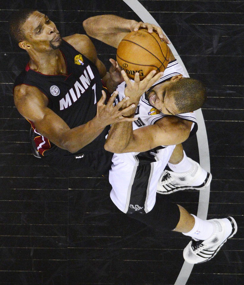 Miami Heat's Chris Bosh and San Antonio Spurs' Tim Duncan go after a rebound during the second half of Game 4 of the NBA Finals basketball series, Thursday, June 13, 2013, in San Antonio. (AP Photo/Larry W. Smith, Pool)