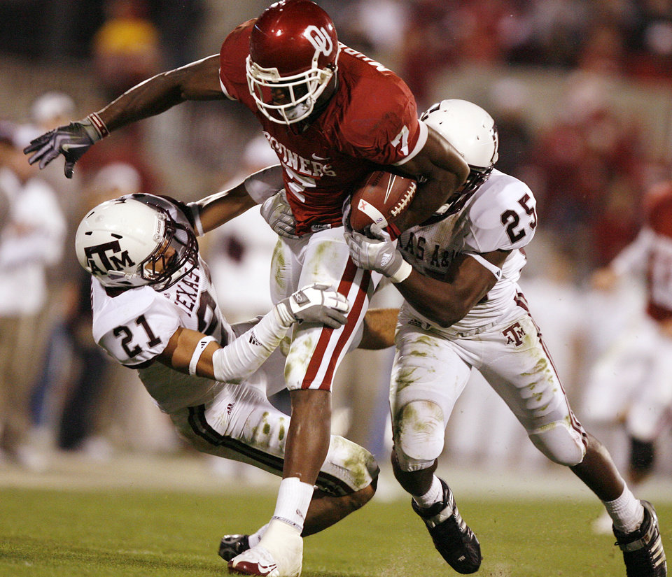 Photo - Oklahoma's DeMarco Murray (7) runs through the tackle of Texas A&M's Justin McQueen (21) and Jordan Pugh (25) during the second half of the college football game between the University of Oklahoma Sooners (OU) and the Texas A&M Aggies at Gaylord Family-Memorial Stadium on Saturday, Nov. 14, 2009, in Norman, Okla. 