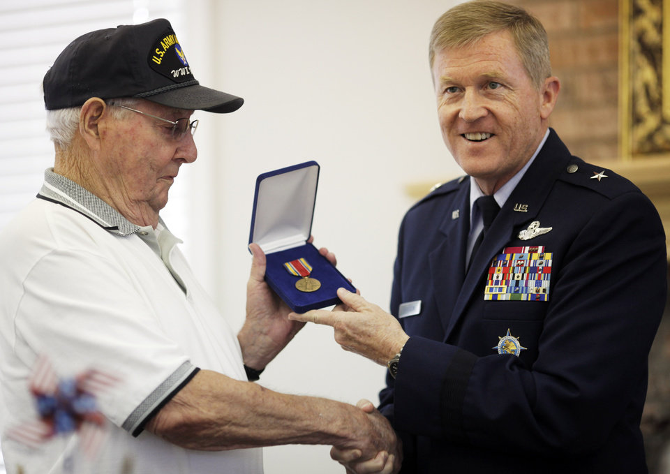 Photo - John Martin (left), a World War II veteran of the Army Air Force, is presented medals by Greg Ferguson, Brigadier General of the Oklahoma Air National Guard, at Martin's 90th birthday party on July 7, 2013. John Martin received three metals, the WWII Victory Medal, American Campaign Medal, and the Army Good Conduct Medal, that he had been awarded in World War II but had not received until 2013. Photo by KT KING, The Oklahoman