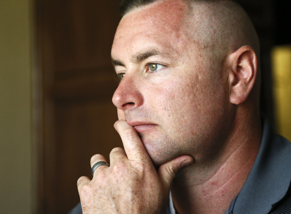 Brandon Douglas listens to his wife, Jennifer Douglas, not pictured, as she gives an interview at their home in Oklahoma City on July 1. Brandon Douglas left the Marines as a Gunnery Sergeant after battling PTSD. Photo by Nate Billings, The Oklahoman <strong>NATE BILLINGS</strong>