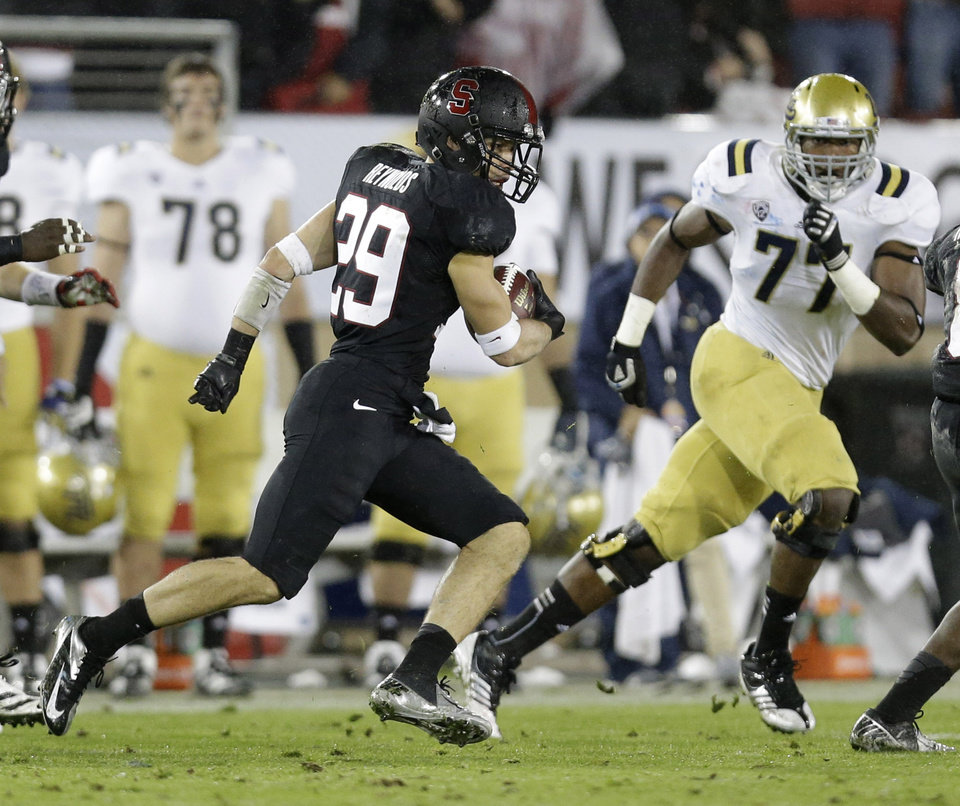 Photo - Stanford safety Ed Reynolds (29) returns an interception for 80 yards against UCLA during the first half of the Pac-12 championship NCAA college football game in Stanford, Calif., Friday, Nov. 30, 2012. (AP Photo/Marcio Jose Sanchez)