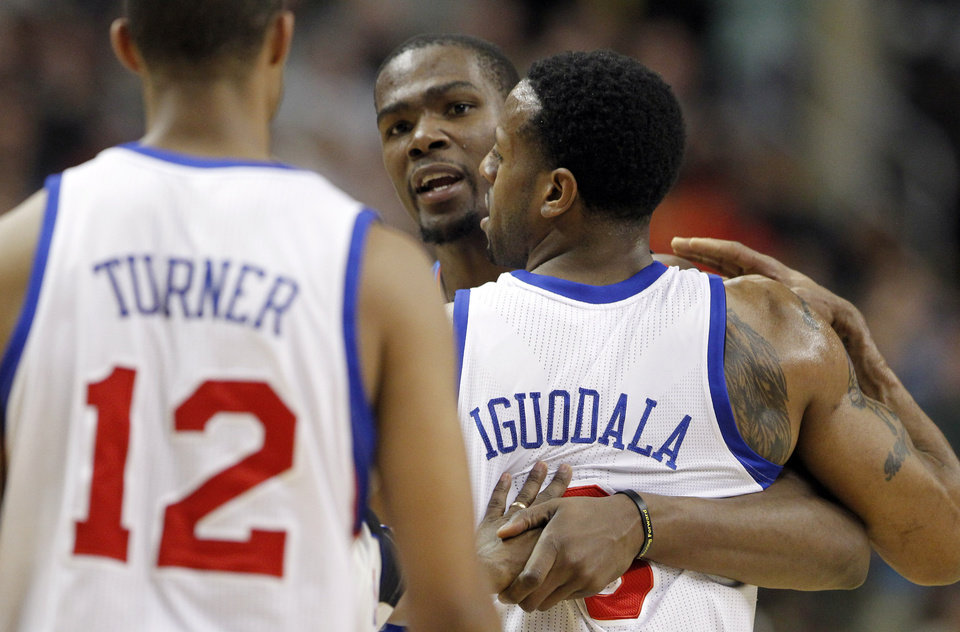 Photo - Oklahoma City Thunder's Kevin Durant, center, is restrained by Philadelphia 76ers' Andre Iguodala (9) to keep him from Evan Turner (12) during the first half of an NBA basketball game on Wednesday, Feb. 29, 2012, in Philadelphia. (AP Photo/Alex Brandon) ORG XMIT: PXC102