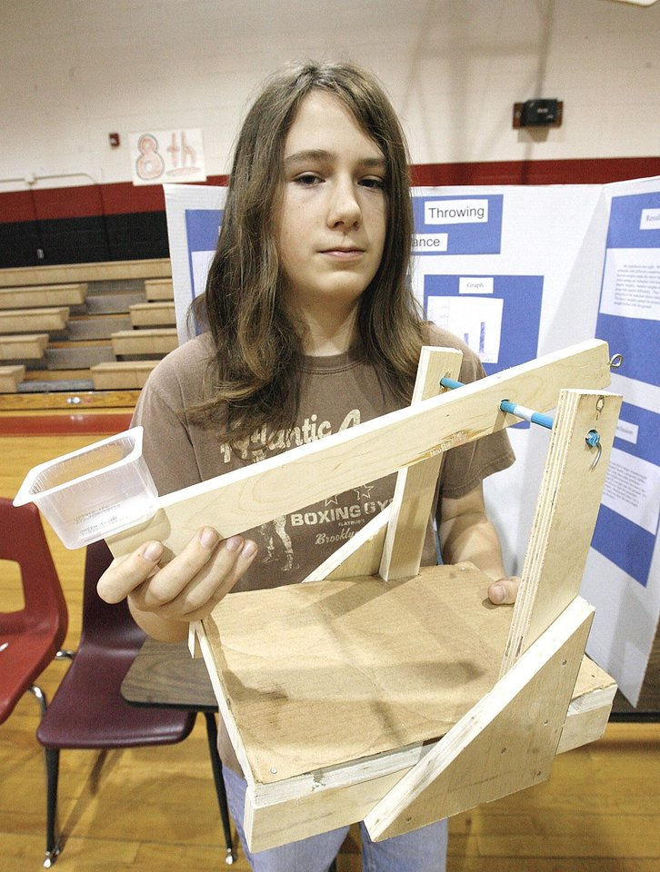 Photo - Left: Eighth-grader Jason Perkins, 14, took second place in the engineering division with the trebuchet  he built.
