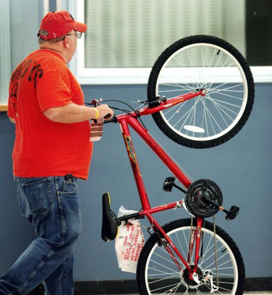 Photo - A volunteer pushes an assembled bicycle to the final inspection area Saturday in Midwest City.