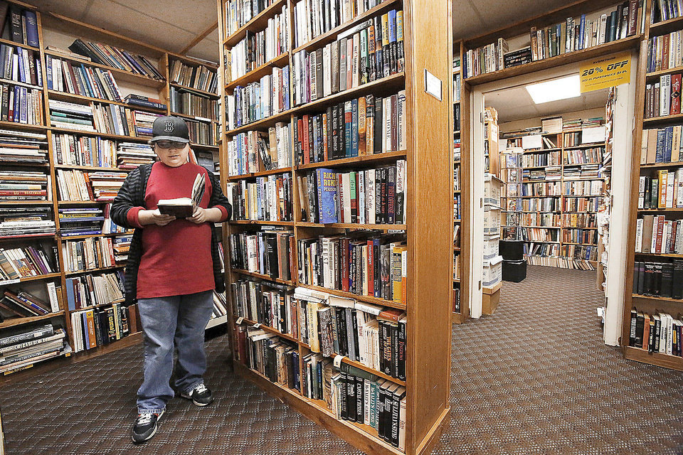 Photo - Zach Olson, 13,  a student at Summit Middle School in Edmond, looks through a large selection of books. Despite a fire that could have destroyed more than 40,000 rare and used books at a landmark Oklahoma City bookstore, Aladdin Book Shoppe remains open for customers last Saturday, Dec. 22, 2012. Photo by Jim Beckel, The Oklahoman