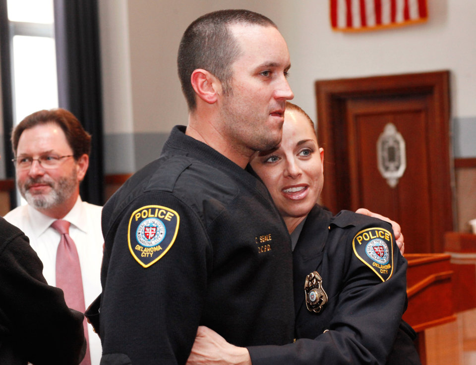 Photo - Officer Katie Lawson hugs another officer as she is greeted by the nearly 40 fellow officers who remained in the courtroom after her shooters were sentenced. At left is Judge Deason. Brothers Alex Mercado and Hector Escalante were given separate sentences by District Judge Donald Deason in an Oklahoma County courtroom Tuesday afternoon, Nov. 8, 2011 for  their involvement in shooting Oklahoma City police officer Katie Lawson during an ambush in south Oklahoma City in Aug, 2010.   Chief Bill Citty and his four assistant chiefs were seated among  nearly 40 uniformed police officers in the courtroom as the sentences were imposed. Several said they came to support Officer Lawson.  Photo by Jim Beckel, The Oklahoman