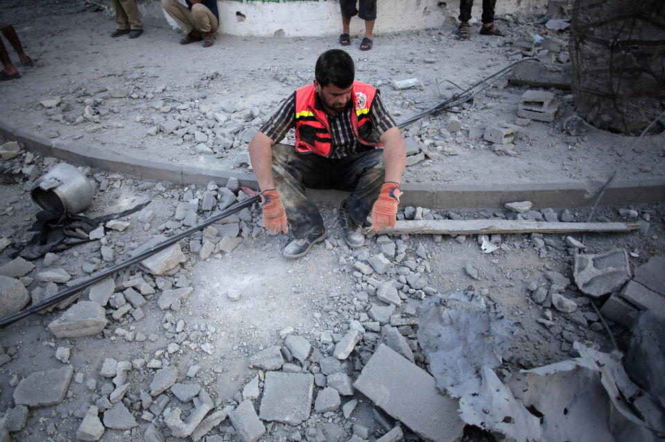 Photo - A Palestinian firefighter restswhile searching for the dead and injured during a two hour temporary ceasefire in Gaza City's Shijaiyah neighborhood, Wednesday, July 23, 2014. Israeli troops battled Hamas militants on Wednesday near a southern Gaza Strip town as the top U.S. diplomat reported progress in efforts to end fighting that has so far killed more than 600 Palestinians and more than 30 Israelis. (AP Photo/Khalil Hamra)
