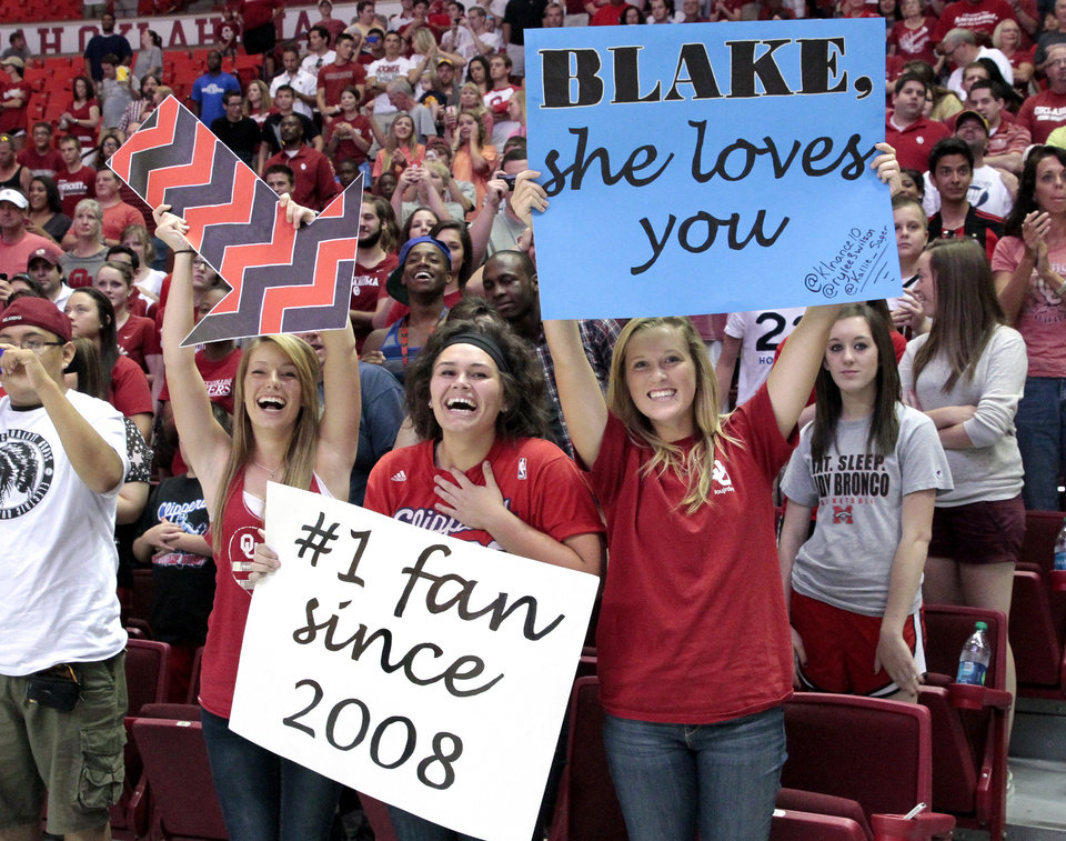 Photo - Fans Rylee Wilson, Kallie Sager, and Kennady Nance hold signs proclaiming Sager's affection toward Blake Griffin as the University of Oklahoma Sooners (OU) basketball alumni play at The Lloyd Noble Center on Saturday, Aug. 24, 2013  in Norman, Okla. Photo by Steve Sisney, The Oklahoman