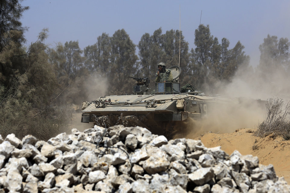 Photo - An Israeli armored personnel carrier returns to Israel from Gaza Strip, southern Israel, Monday, Aug. 4, 2014. A brief cease-fire declared by Israel and troop withdrawals slowed violence in the Gaza war Monday, but an attack on an Israeli bus that killed one person in Jerusalem underscored the tensions still simmering in the region as Israeli airstrikes resumed late in the day. (AP Photo/Tsafrir Abayov)