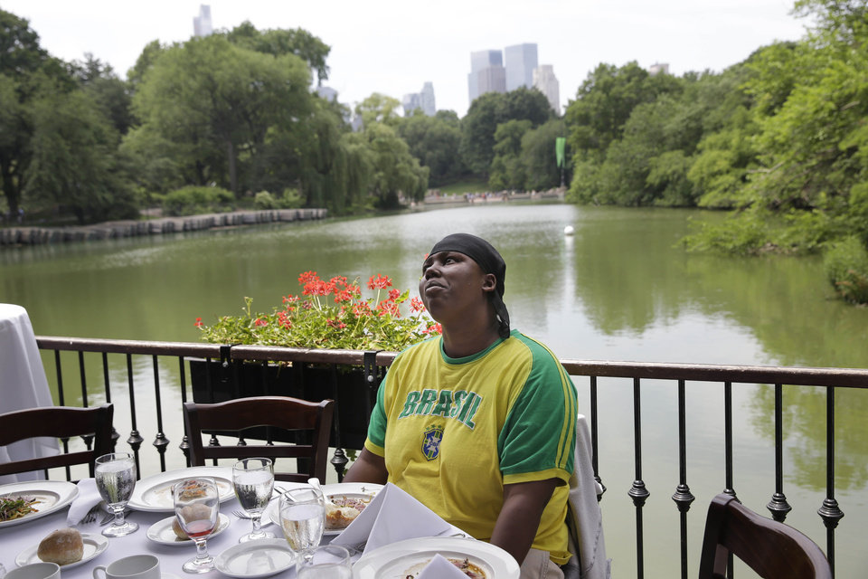Photo - Shatima Davis, an occasional resident of the New York Rescue Mission, enjoys an appetizer at The Loeb Boathouse restaurant in New York, Wednesday, June 25, 2014. Recycling magnate Chen Guangbiao,  known for his sometimes eccentric gestures served up a fancy lunch Wednesday to hundreds of homeless New Yorkers at a Central Park restaurant and serenaded them with
