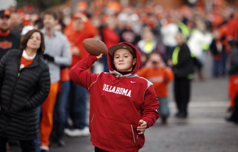 Photo - OU fan Jace Rosser, 12, of Edmond, Okla., tosses the football with friend and OSU fan Karsten Menard (not pictured), 11, also of Edmond, while waiting for the Spirit Walk before the Bedlam college football game between the Oklahoma State University Cowboys (OSU) and the University of Oklahoma Sooners (OU) at Boone Pickens Stadium in Stillwater, Okla., Saturday, Dec. 3, 2011. Photo by Nate Billings, The Oklahoman