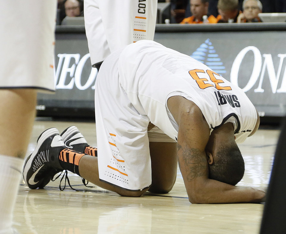 Photo - Oklahoma State 's Marcus Smart (33) is injured in the second overtime after fouling out during the college basketball game between the Oklahoma State University Cowboys (OSU) and the University of Kanas Jayhawks (KU) at Gallagher-Iba Arena on Wednesday, Feb. 20, 2013, in Stillwater, Okla. Photo by Chris Landsberger, The Oklahoman