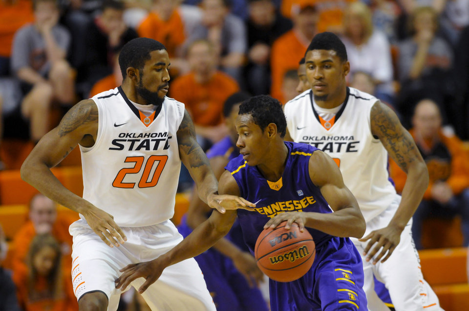 Oklahoma State guard Marcus Smart, right, watches as teammate forward Michael Cobbins, left, attempts to steal the ball from Tennessee Tech guard Jud Dillard, center, during the second half of an NCAA college basketball game in Stillwater, Okla., Saturday, Dec. 22, 2012. Dillard scored 18 in the 42-78 loss to Oklahoma State. (AP Photo/Brody Schmidt) ORG XMIT: OKBS106