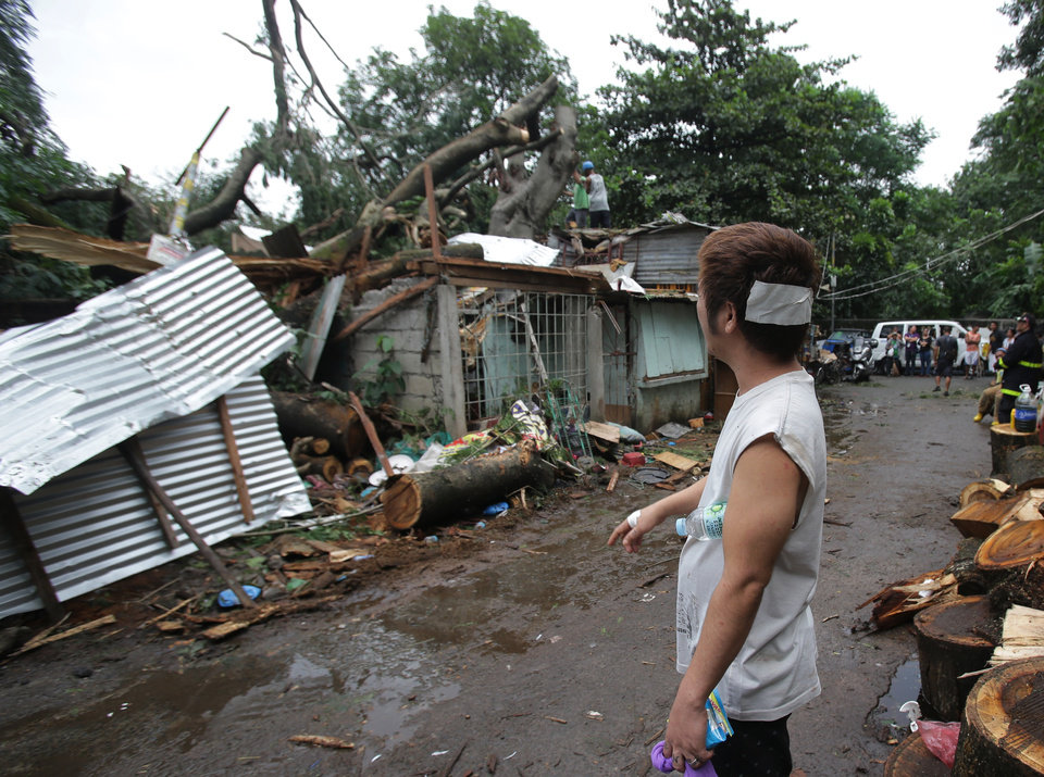 Photo - Injured resident Arnel Castillo looks at the damage to his home caused by a fallen tree from Typhoon Koppu in suburban Quezon city, north of Manila, Philippines on Monday, Oct. 19, 2015. Army, police and civilian volunteers scrambled Monday to rescue hundreds of villagers trapped in flooded homes and on rooftops in the northern Philippine province battered by slow-moving Typhoon Koppu. (AP Photo/Aaron Favila)