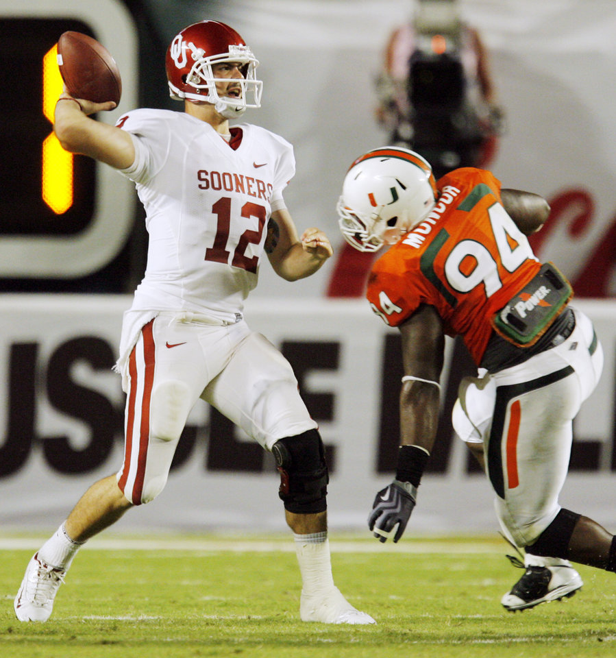 Photo - OU's Landry Jones (12) passes under pressure from Miami's Eric Moncur (94) during the college football game between the University of Oklahoma (OU) Sooners and the University of Miami (UM) Hurricanes at Land Shark Stadium in Miami Gardens, Florida, Saturday, October 3, 2009. Miami won, 21-20. The pass fell incomplete. Photo by Nate Billings, The Oklahoman