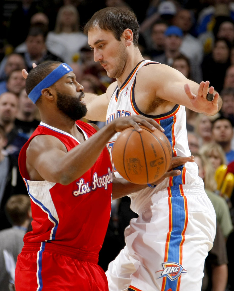 Photo - Oklahoma City's Nenad Krstic (12) defends Los Angeles' Baron Davis (5) during the NBA basketball game between the Oklahoma City Thunder and the Los Angeles Clippers at the Oklahoma CIty Arena, Tuesday, Feb. 22, 2011.  Photo by Bryan Terry, The Oklahoman