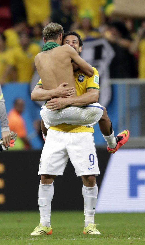 Photo - Brazil's Neymar celebrates with his teammate Fred after  a 4-1 win over Cameroon during the group A World Cup soccer match between Cameroon and Brazil at the Estadio Nacional in Brasilia, Brazil, Monday, June 23, 2014. (AP Photo/Dolores Ochoa)