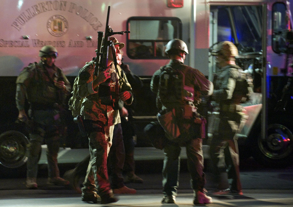 SWAT team members form up near a command post south of the Cal State Fullerton campus, Wednesday, Dec. 12, 2012, in Fullerton, Calif. Students were placed on lock down as police searched for two suspects in a jewelry store robbery, who were considered armed and dangerous. (AP Photo/The Orange County Register, Bruce Chambers)