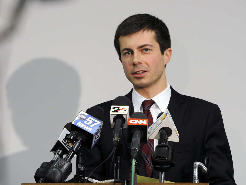 Photo - South Bend Mayor Peter Buttigieg speaks to reporters on Monday March 18, 2013, about a Sunday plane crash in South Bend, Ind. Former Oklahoma quarterback Steve Davis and friend Wes Caves were the flight crew for the private jet that crashed into a northern Indiana neighborhood, killing Davis and Caves and injuring three others. (AP Photo/Joe Raymond)