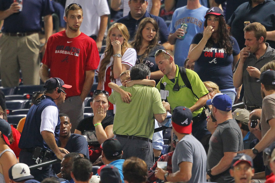 Photo - In this Tuesday, May 20, 2014 photo, fans react as a young boy is picked up by his father and rushed up the steps after being hit by a foul ball off the bat of Milwaukee Brewers' Carlos Gomez in the seventh inning of a baseball game against the Atlanta Braves in Atlanta. The 8-year-old boy who was struck in the head has been released from the hospital and is