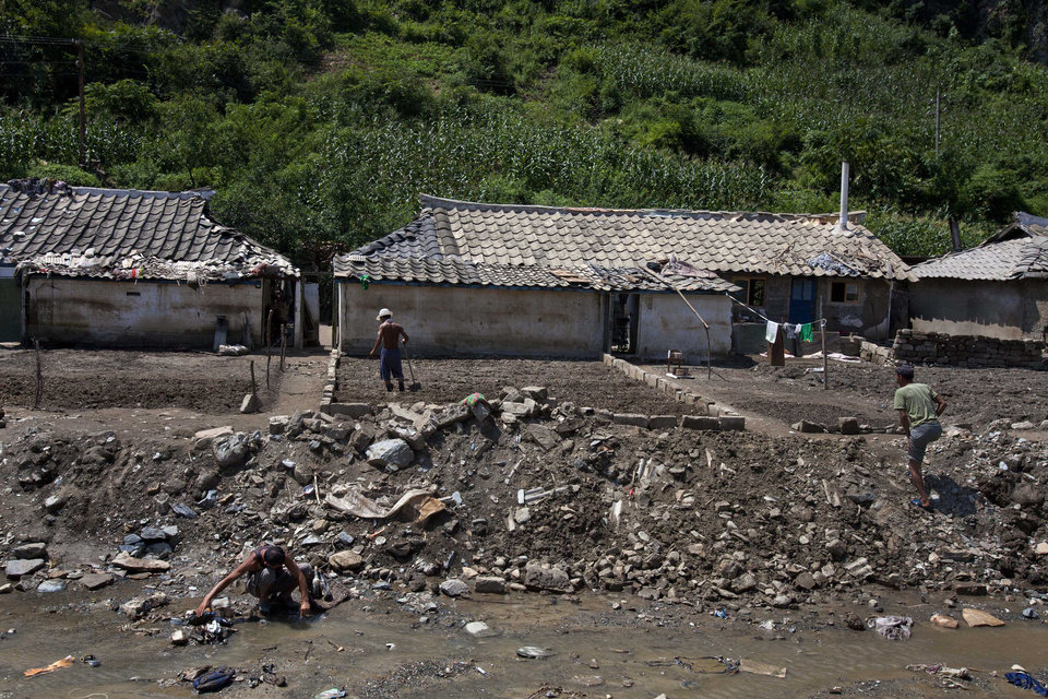 Photo -   In this Monday, Aug 13, 2012 photo, North Koreans sift through their belongings near their homes, damaged by July 2012 flooding, in Ungok, North Korea. Twin typhoons are renewing fears of a humanitarian crisis in North Korea, where poor drainage, widespread deforestation and fragile infrastructure can turn even a routine rainstorm into a catastrophic flood. (AP Photo/David Guttenfelder)