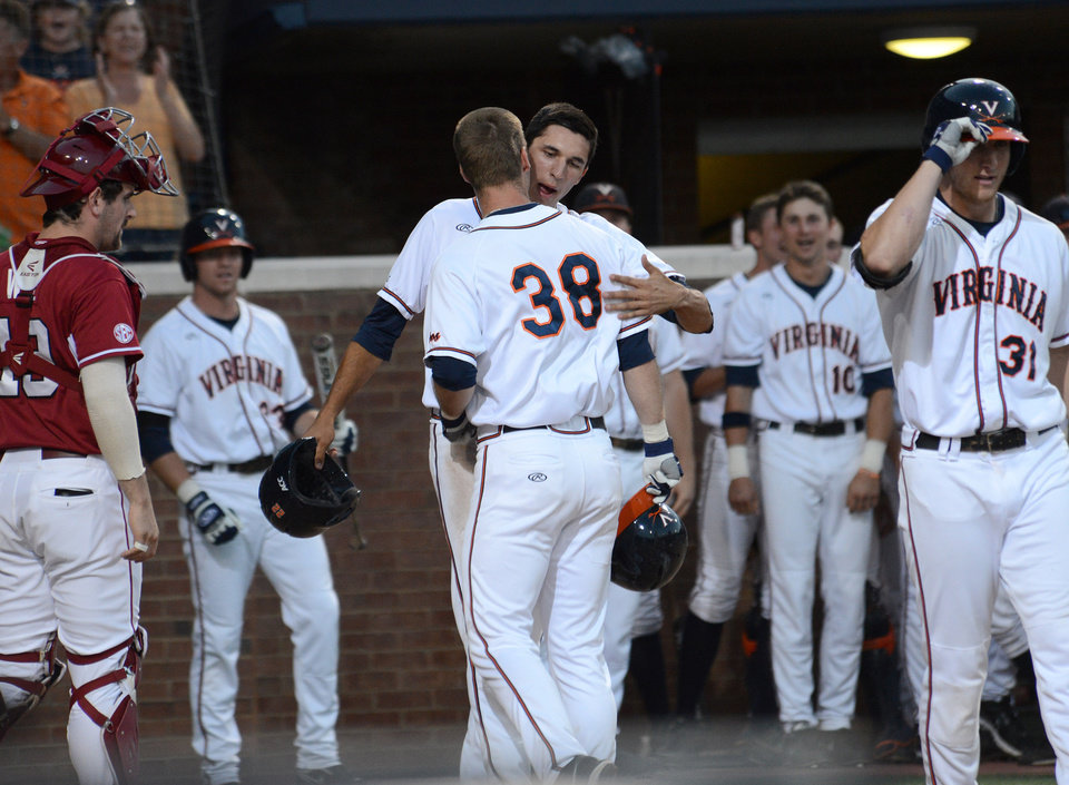 Photo - Teammates congratulate Virginia's Mike Papi (38) as he crosses home plate after hitting a two-run home run during the first inning of an NCAA college baseball regional tournament game against Arkansas in Charlottesville, Va., Saturday, May 31, 2014. (AP Photo/Pat Jarrett)
