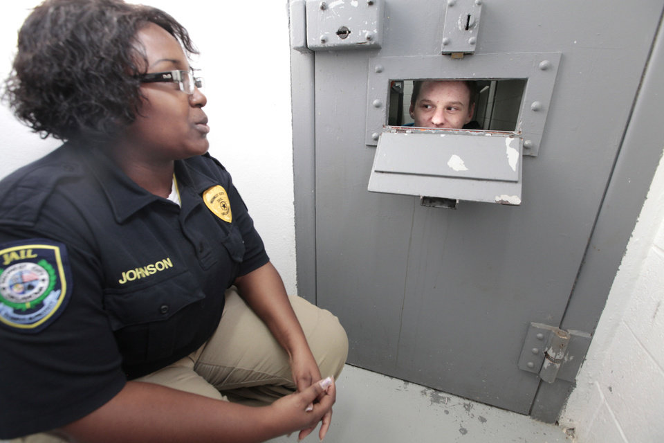 Photo - Midwest City jailer Chanitha Johnson  visits with inmate James Sherfield through a slot in the door of his cell. Midwest City officials are working together with the state's mental health agency to start a new jail diversion program. It's similar to drug court or mental health court but on a city level.  David McDaniel - The Oklahoman