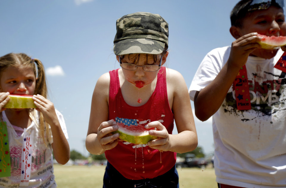 Eight-year-old Emily Winstead of Midwest City takes a bite of watermelon during a watermelon-eating contest at the McLoud Blackberry Festival on Saturday, July 2, 2011, in McLoud, Okla. Photo by Bryan Terry, The Oklahoman
