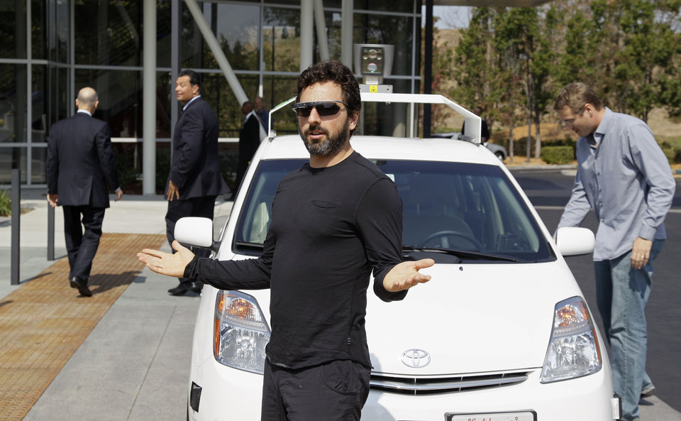 Photo -   Google co-founder Sergey Brin gestures after riding in a driverless car with California Gov. Edmund G Brown Jr., left, and state Senator Alex Padilla, second from left, to a bill signing for driverless cars at Google headquarters in Mountain View, Calif., Tuesday, Sept. 25, 2012. The legislation will open the way for driverless cars in the state. Google, which has been developing autonomous car technology and lobbying for the legislation has a fleet of driverless cars that has logged more than 300,000 miles (482,780 kilometers) of self-driving on California roads. (AP Photo/Eric Risberg)