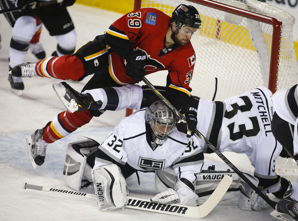 Photo - Los Angeles Kings goalie Jonathan Quick, center, ducks as teammate Willie Mitchell, right, and Calgary Flames' TJ Galiardi crash over him during the first period of an NHL hockey game Thursday, Feb. 27, 2014, in Calgary, Alberta. (AP Photo/The Canadian Press, Jeff McIntosh)