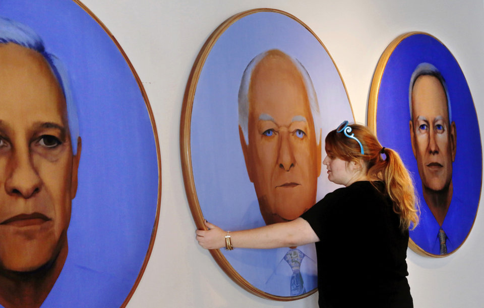 Photo -      Kendall Brown, executive director, Individual Artists of Oklahoma, adjusts paintings of three Oklahoma City mayors by Richard McKown. An exhibit in honor of the 20th anniversary of MAPS is planned on Film Row. Photo by Jim Beckel, The Oklahoman   Jim Beckel -