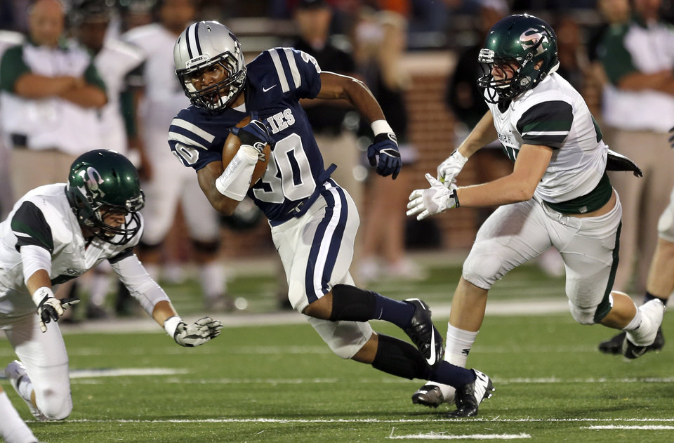 Photo - Edmond North's Richard McCauley runs up field in between two Edmond Santa Fe defenders during the high school football game between Edmond North High School and Edmond Santa Fe High School at Wantland Stadium in Edmond, Okla.,  Friday, Sept. 20, 2013. Photo by Sarah Phipps, The Oklahoman