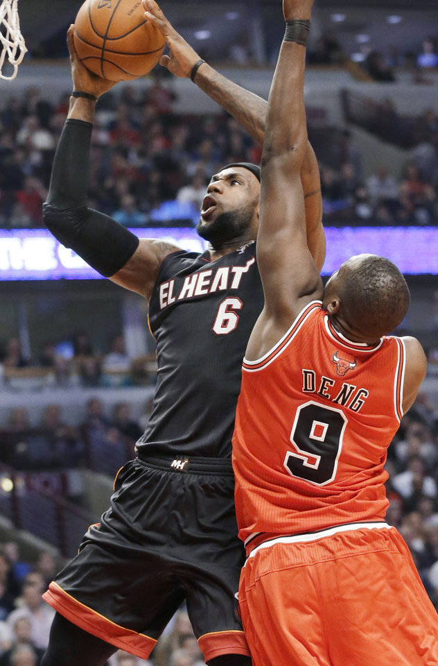Miami Heat forward LeBron James, left, shoots in front of Chicago Bulls forward Luol Deng during the first half of an NBA basketball game in Chicago on Wednesday, March 27, 2013. (AP Photo/Nam Y. Huh)