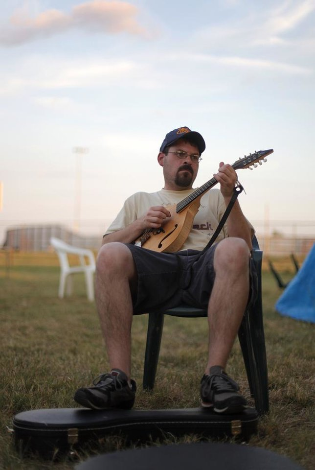 Photo -  Jeff Clanton plays mandolin near his camp during the Woody Guthrie Folk Festival in Okemah, Okla., Thursday, July 12, 2012.  Photo by Garett Fisbeck, The Oklahoman