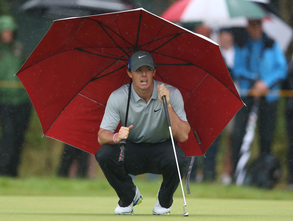 Photo - Rory McIlroy of Northern Ireland kneels under an umbrella as he waits to play on the 4th green during the third day of the British Open Golf championship at the Royal Liverpool golf club, Hoylake, England, Saturday July 19, 2014. (AP Photo/Jon Super)
