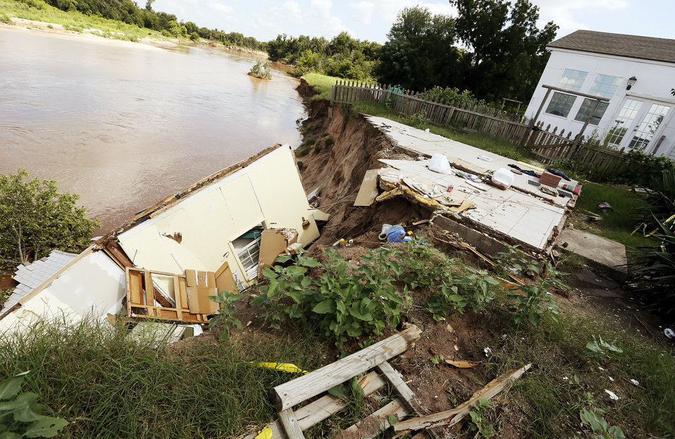 Photo - The smaller of Gary and Rhonda Buford's two houses has slid into the North Canadian River in Choctaw. Photo by Nate Billings, The Oklahoman  NATE BILLINGS - NATE BILLINGS