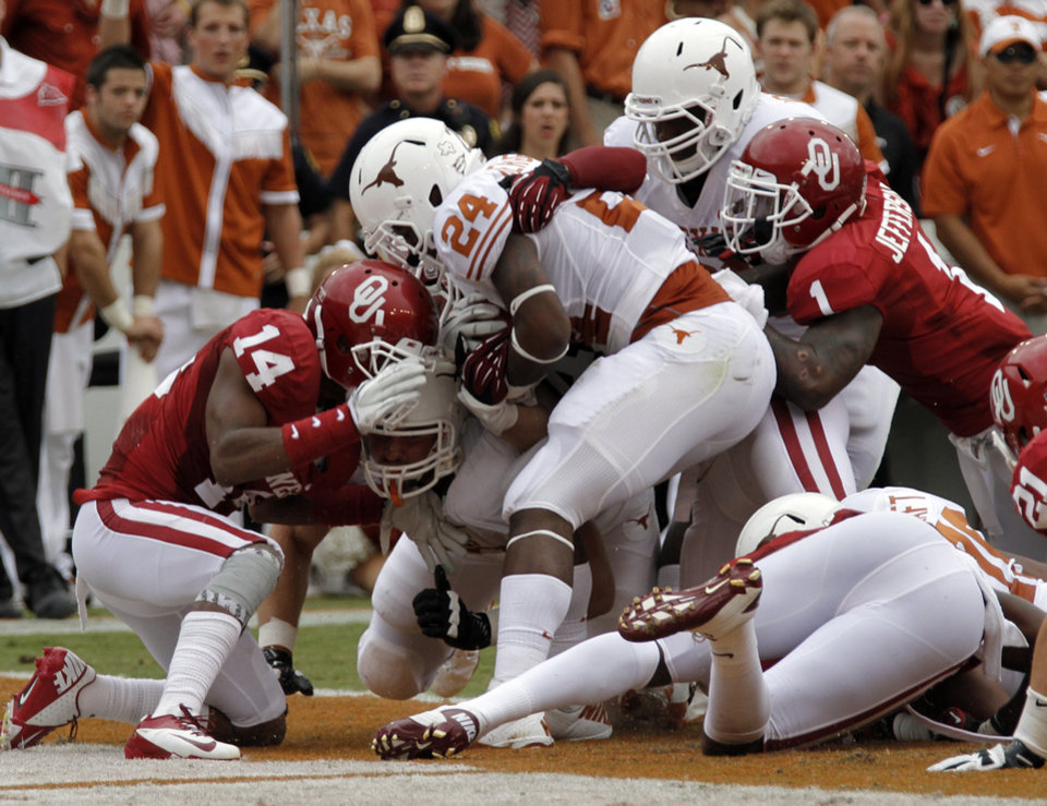 OU's Aaron Colvin (14) and OU's Tony Jefferson (1) get a safety on Joe Bergeron (24) during the Red River Rivalry college football game between the University of Oklahoma (OU) and the University of Texas (UT) at the Cotton Bowl in Dallas, Saturday, Oct. 13, 2012. Photo by Chris Landsberger, The Oklahoman