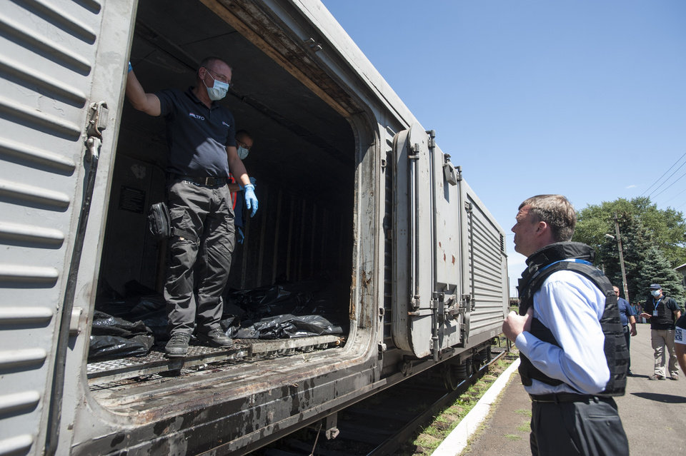Photo - Deputy head of the OSCE mission to Ukraine Alexander Hug, right, speaks to a member of Netherlands' National Forensic Investigations team on the platform as a refrigerated train loaded with bodies of the passengers departs the station in Torez, eastern Ukraine, 15 kilometers (9 miles) from the crash site of Malaysia Airlines Flight 17, Monday, July 21, 2014. Another 21 bodies have been found in the sprawling fields of east Ukraine where Malaysia Airlines Flight 17 was downed last week, killing all 298 people aboard. International indignation over the incident has grown as investigators still only have limited access to the crash site and it remains unclear when and where the victims' bodies will be transported. (AP Photo/Evgeniy Maloletka)