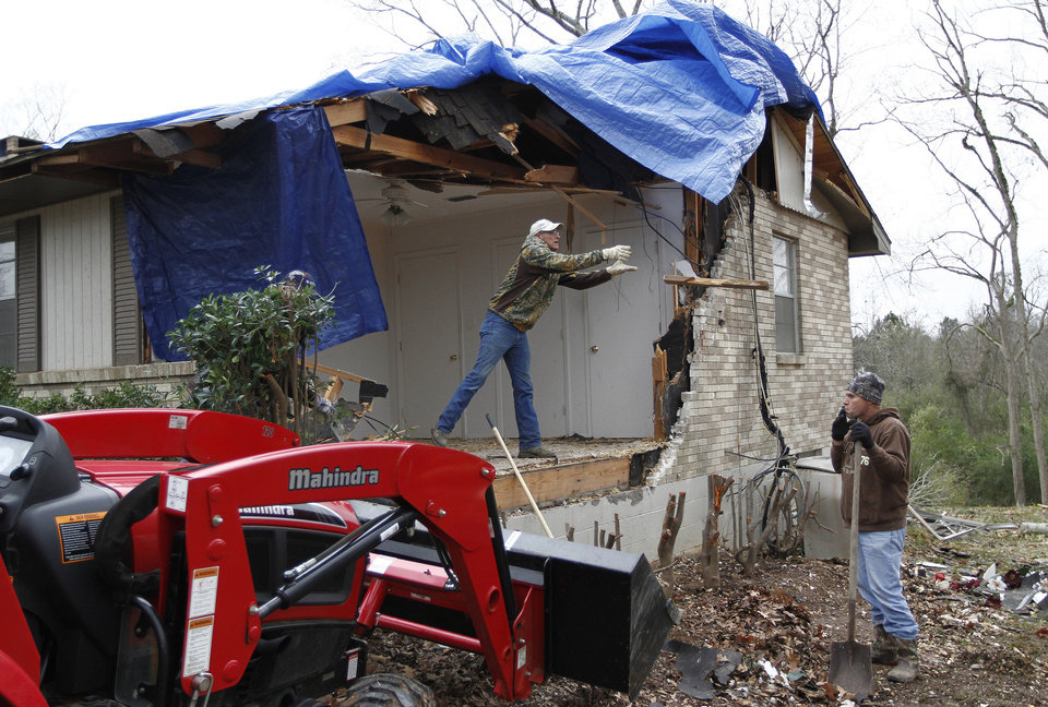 Photo - Michael Donaldson, left, and Michael Lane work on clearing away damage done to the home of John Templeton in Centreville, Miss. on Wednesday, Dec. 26, 2012. Templeton said there were four people at home at the time of the storm, all were unharmed after seeking shelter in the basement. More than 25 people were injured and at least 70 homes were damaged in Mississippi by the severe storms that pushed across the South on Christmas Day, authorities said Wednesday. (AP Photo/The Enterprise-Journal, Philip Hall)